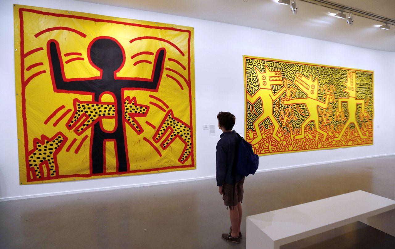 This picture taken on April 17, 2013 shows a spectator looking at an untitled art creation by US artist Keith Haring at the Musee d'Art Moderne (Modern Art Museum), in Paris, two days before the opening of an exhibition dedicated to Haring's work, 23 years after his death. The exhibition will last from April 19 to August 18. AFP PHOTO / FRANCOIS GUILLOT RESTRICTED TO EDITORIAL USE, MANDATORY MENTION OF THE ARTIST UPON PUBLICATION, TO ILLUSTRATE THE EVENT AS SPECIFIED IN THE CAPTION