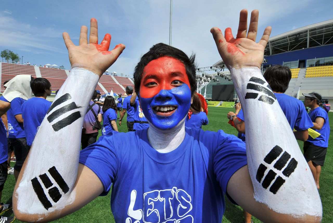 A South Korean university student cheers to support Pyeongchang's bid for the 2018 Winter Olympics at a ski jump stadium in the mountain resort of Pyeongchang, 180 kms east of Seoul, on July 6, 2011. The students will join a cheering night rally by local residents while watching the live TV coverage of an IOC vote in the South African city of Durban. TOPSHOTS AFP PHOTO/JUNG YEON-JE