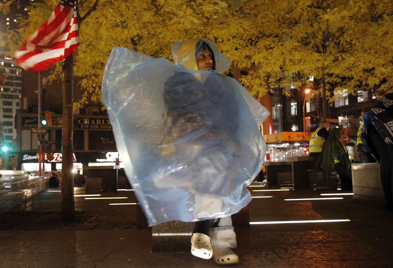 An Occupy Wall Street protester wrapped in a poncho sits on a bench after being allowed to re-enter New York's Zuccotti Park November 15, 2011. A judge upheld New York City's legal justification for evicting Occupy Wall Street protesters from the park on Tuesday when police in riot gear broke up a two-month-old demonstration against economic inequality. REUTERS/Jessica Rinaldi (UNITED STATES - Tags: BUSINESS CIVIL UNREST POLITICS)