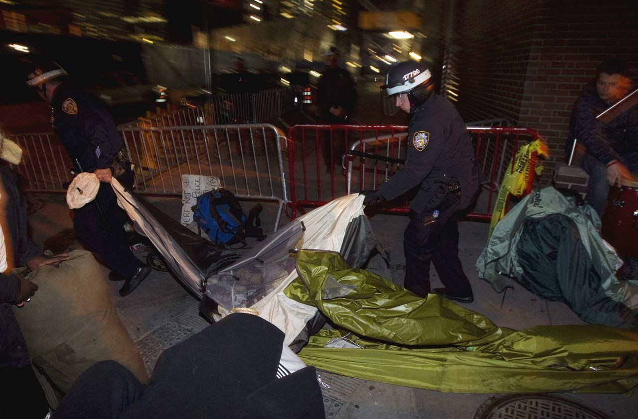 New York Police Department officers remove the belongings of members of the Occupy Wall Street movement after removing members of the movement from Zuccotti Park in New York November 15, 2011. Police wearing helmets and carrying shields early on Tuesday began to clear the park in New York City's financial district, where protesters from the movement have been camping since September. REUTERS/Lucas Jackson (UNITED STATES - Tags: BUSINESS CIVIL UNREST CRIME LAW)