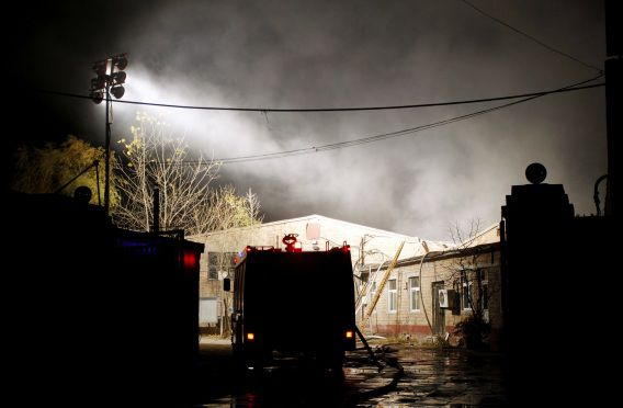 Een brandweerwagen voor de opslagplaats die vannacht in brand vloog in Beijing.