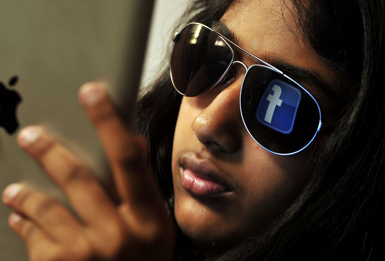 The 'Facebook' logo is reflected in a young Indian woman's sunglasses as she browses on a tablet in Bangalore on May 15, 2012. World's popular and leading social networking company Facebook Inc., founded in a Harvard dorm room by Mark Zuckerberg whose current value exceeds 100 billion USD, will be making an initial public offering (IPO) which is slated to be Silicon Valley's biggest-ever. AFP PHOTO/Manjunath KIRAN