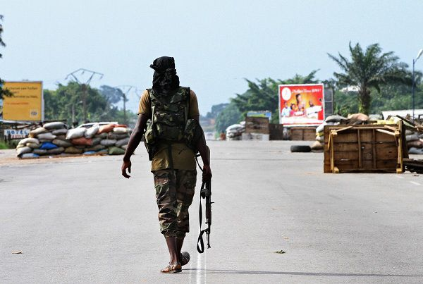 """A pro-Ouattara fighter from a group which calls itself the """"invisible commandos"""" walks on a street in northern Abidjan's Abobo district March 26, 2011. Fighting in Ivory Coast's main city is spreading and the death toll from a power struggle between incumbent leader Laurent Gbagbo and his rival Alassane Ouattara is mounting. REUTERS/Luc Gnago (IVORY COAST - Tags: CIVIL UNREST POLITICS)"""