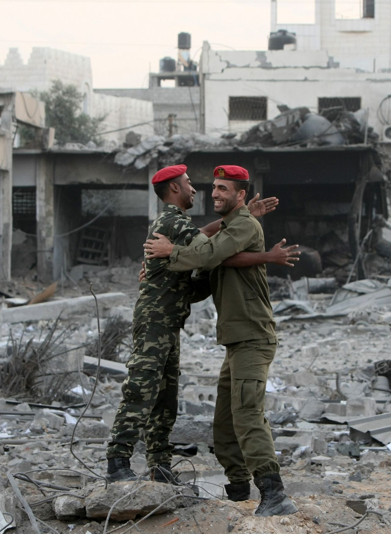 Hamas police officers embrace after their return to their destroyed Al-Saraya headquarters in Gaza City November 22, 2012, a day after a cease fire was declared between Israel and Hamas. An Egypt-brokered truce took hold in the Gaza Strip after a week of bitter fighting between militant groups and Israel, with both sides claiming victory but remaining wary. AFP PHOTO/MAHMUD HAMS
