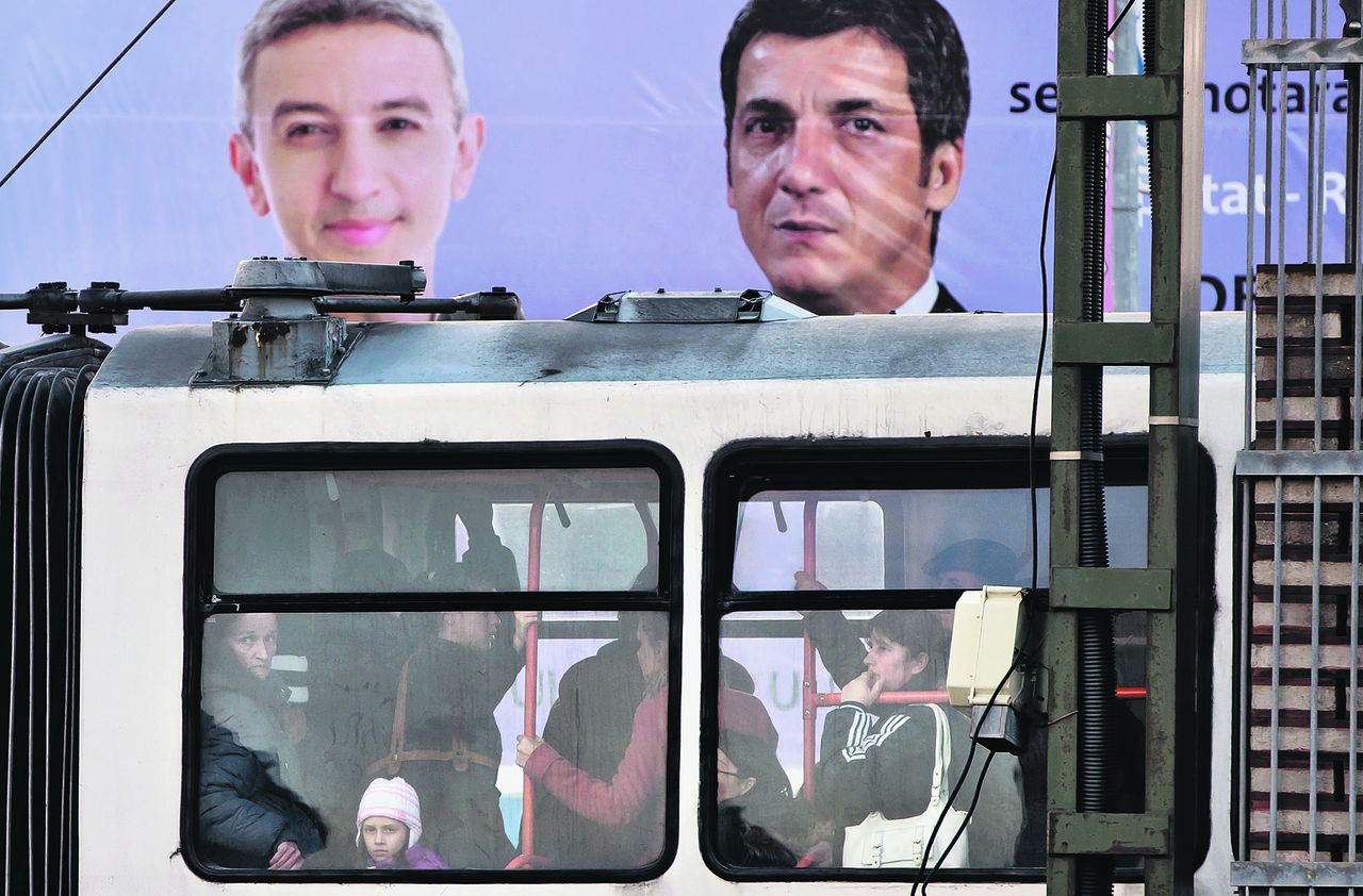 People riding on a tram are backdropped by a large electoral poster of the populist People's Party in Bucharest, Romania, Wednesday, Dec. 5, 2012. Romania will hold parliamentary elections on Dec. 9, 2012. (AP Photo/Vadim Ghirda)