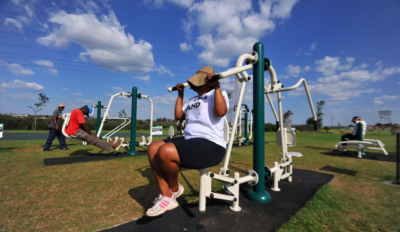 TO GO WITH AFP STORY SAfrica-health-gym-fat-lifestyle,FEATURE BY SIBONGILE KHUMALO In this photograph taken on on March 19, 2012, people work out at new outdoor gym in Soweto. The facility, set in a park among tiny two-bedroom homes, has caught on with many Sowetans who are determined to lose the flab without signing expensive gym contracts. Opened by the Johannesburg city council a month ago, the gym has seen the people of all ages pumping iron and swaying around in swing-like contraptions designed to target problem fat. AFP PHOTO / ALEXANDER JOE