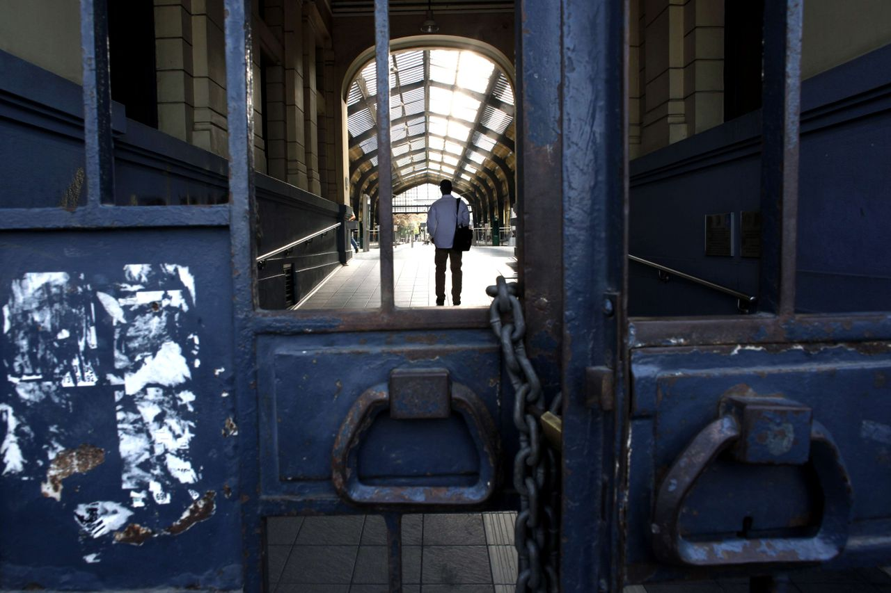 TOPSHOTS A man stands inside an empty train station in Athens on July 17, 2012. The employees of Electric Railways (ISAP) proceed to a four-hour strike as they protest against the merging of the insurance fund institutions. AFP PHOTO / Angelos Tzortzinis