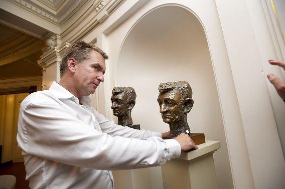 Melle Daamen, directeur van de Amsterdamse Stadsschouwburg, bij het originele bronzen beeld van Simon Carmiggelt.