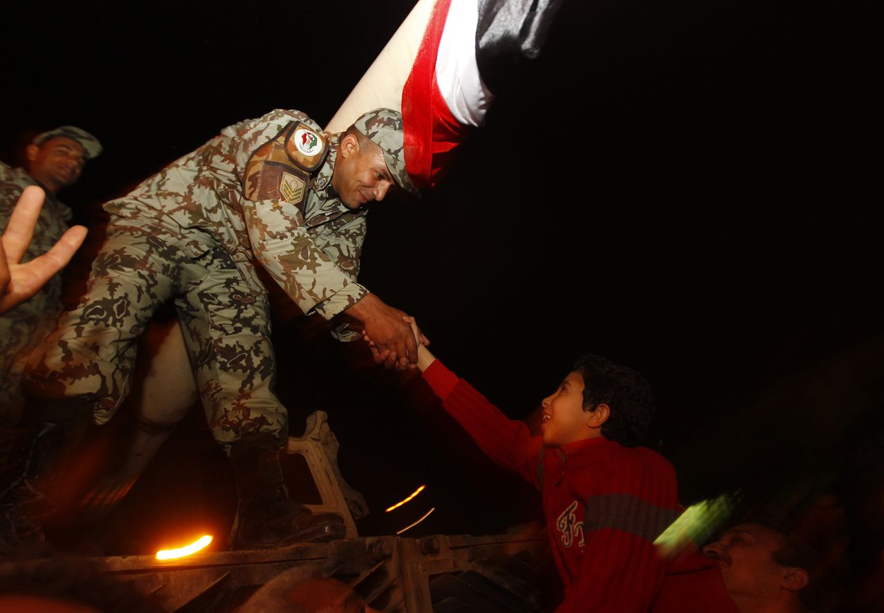 A young Egyptian is raised by his father to shake hands with an army officer atop a tank in Tahrir square in Cairo February 11, 2011. A furious wave of protest finally swept Egypt's President Hosni Mubarak from power on Friday after 30 years of one-man rule, sparking jubilation on the streets and sending a warning to autocrats across the Arab world and beyond. REUTERS/Yannis Behrakis (EGYPT - Tags: CIVIL UNREST POLITICS MILITARY IMAGES OF THE DAY)