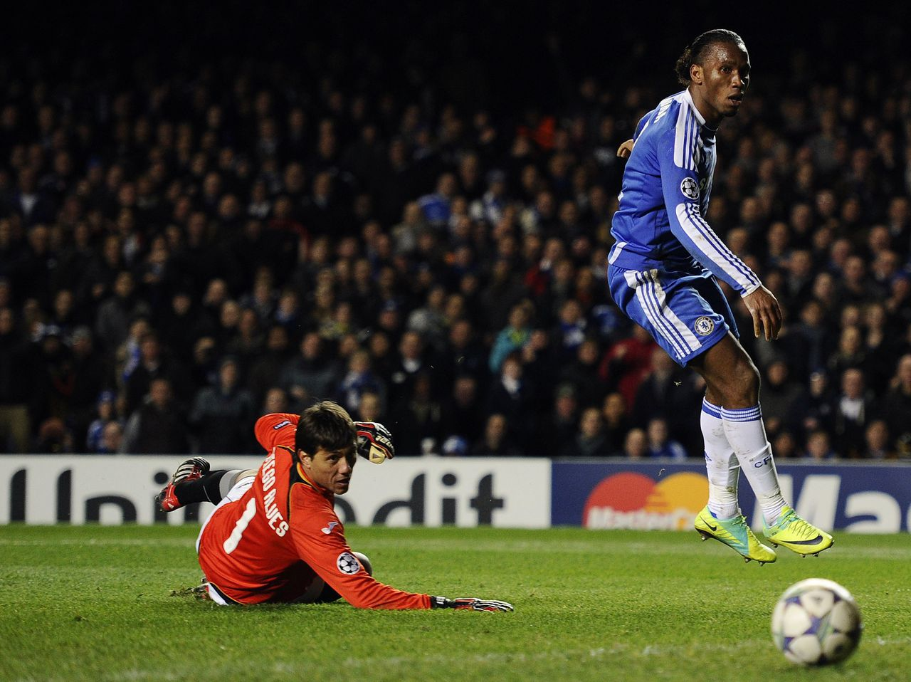 Chelsea's Didier Drogba (R) scores against Valencia's goalkeeper Diego Alves during their Champions League Group E soccer match at Stamford Bridge in London December 6, 2011. REUTERS/Dylan Martinez (BRITAIN - Tags: SPORT SOCCER)
