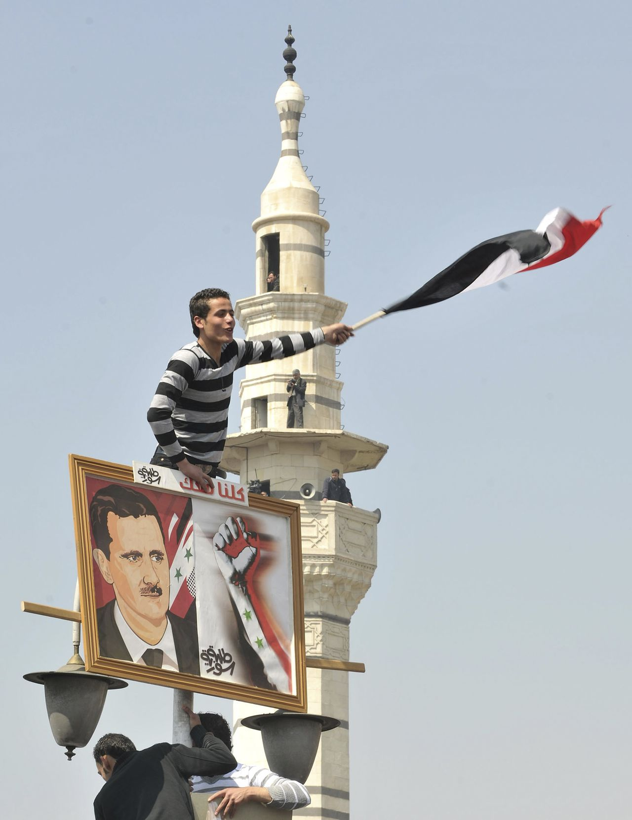 A Syrian man waves the national flag while holding a picture of Syria's President Bashar al-Assad during a pro-government rally at the central bank square in Damascus March 29, 2011. Assad accepted his government's resignation on Tuesday after nearly two weeks of pro-democracy unrest that has posed the gravest challenge to his 11-year rule. REUTERS/Wael Hmedan (SYRIA - Tags: CIVIL UNREST POLITICS)