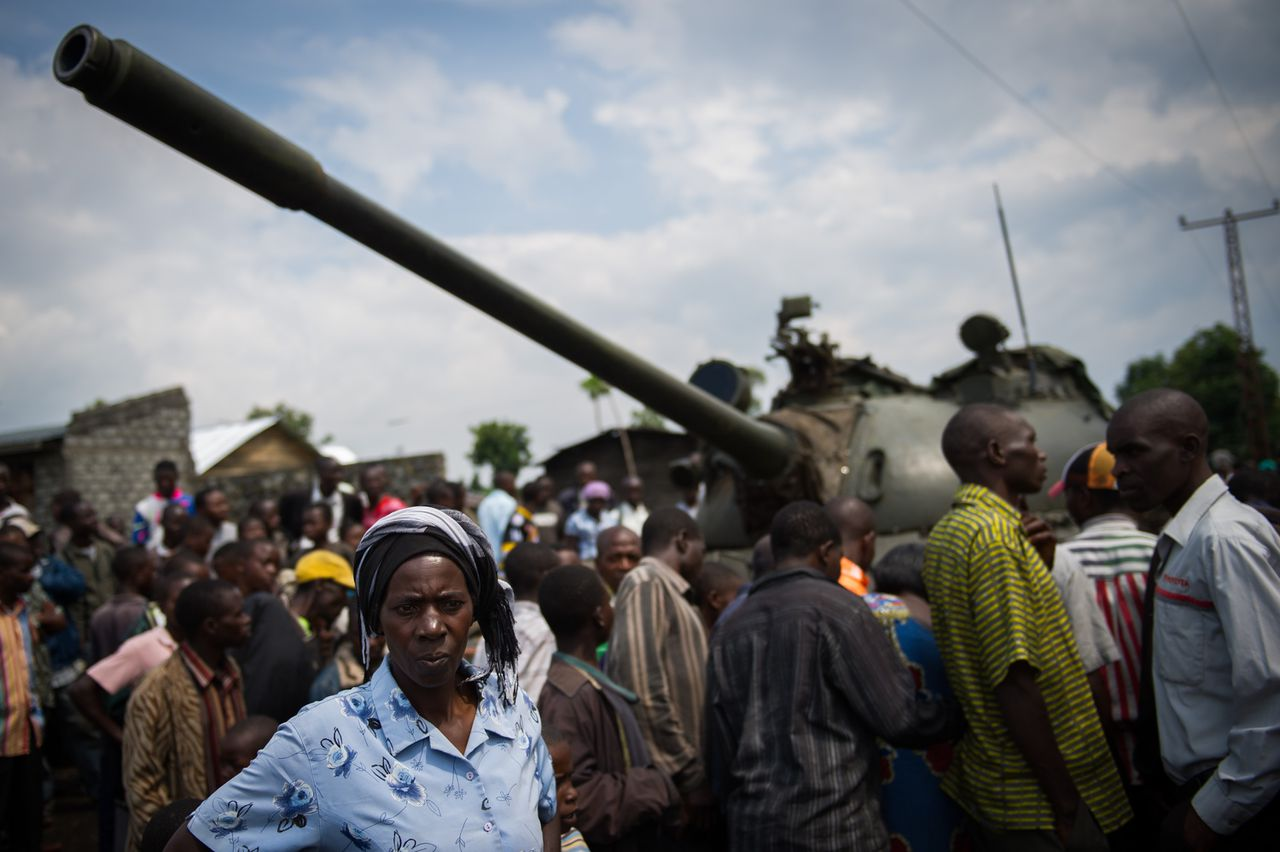 A resident of the Ndosho district of Goma stands in a crowd formed around a tank left by retreating government troops in the east of the Democratic Republic of the Congo on November 21, 2012.The lightning seizure by rebels of Democratic Republic of Congo's city of Goma is a blow for President Joseph Kabila, but how far fighters will press forward their advantage is not clear, analysts say. AFP PHOTO/PHIL MOORE