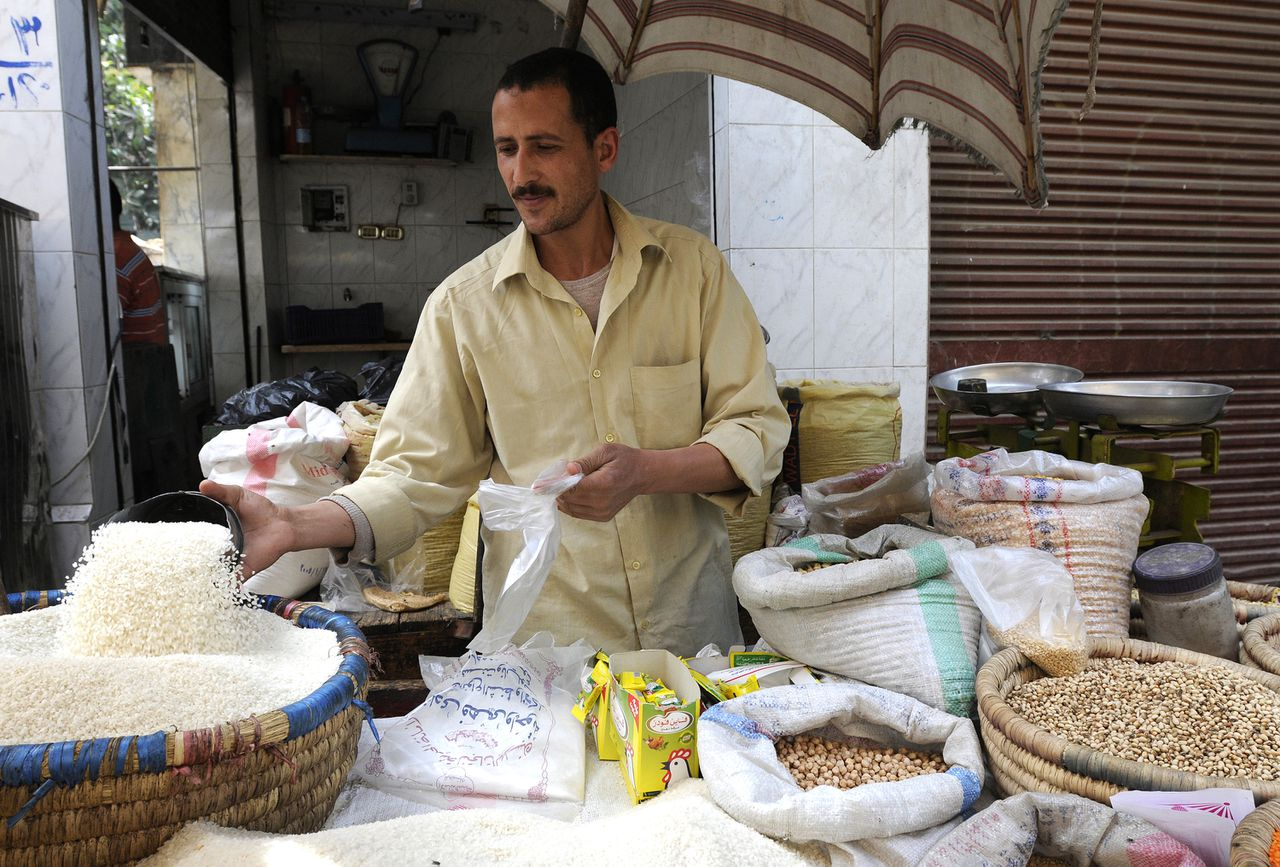 A street trader scoops a measure of locally grown rice at a market in Cairo, Egypt, on Sunday, April 13, 2008. Rice jumped to a record as World Bank officials said they are concerned pressure is growing in Thailand, the world's largest exporter, to restrict shipments, worsening a global food crisis. Photographer: Dana Smillie/Bloomberg News.