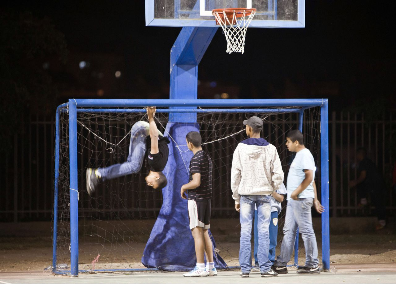 Youths play at an outdoor court in Lod May 6, 2012. The backstreets of Lod, a mixed Arab-Jewish city just 20 minutes from the tree-lined boulevards of Tel Aviv, reveal a seamy underside of Israel that few visitors get to see, tucked away behind Ben Gurion airport off the main highway to Jerusalem and the occupied West Bank. Picture taken May 6, 2012. To match Feature ISRAEL-ARABS/CRIME REUTERS/Nir Elias (ISRAEL - Tags: SOCIETY)