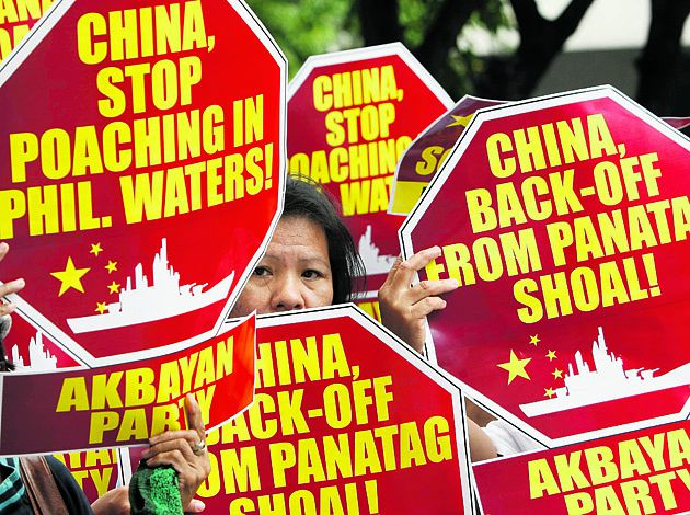 Protesters display placards during their rally outside the Chinese Consulate at the financial district of Makati city, east of Manila, Philippines Monday, April 16, 2012, to accuse poaching by Chinese fishermen that led to a military standoff at the disputed Scarborough Shoal in the South China Sea. The Philippine president said Monday his country will continue talks with China to resolve the impasse, which began last Tuesday when two Chinese ships prevented a Philippine warship from arresting several Chinese fishermen. (AP Photo/Bullit Marquez)