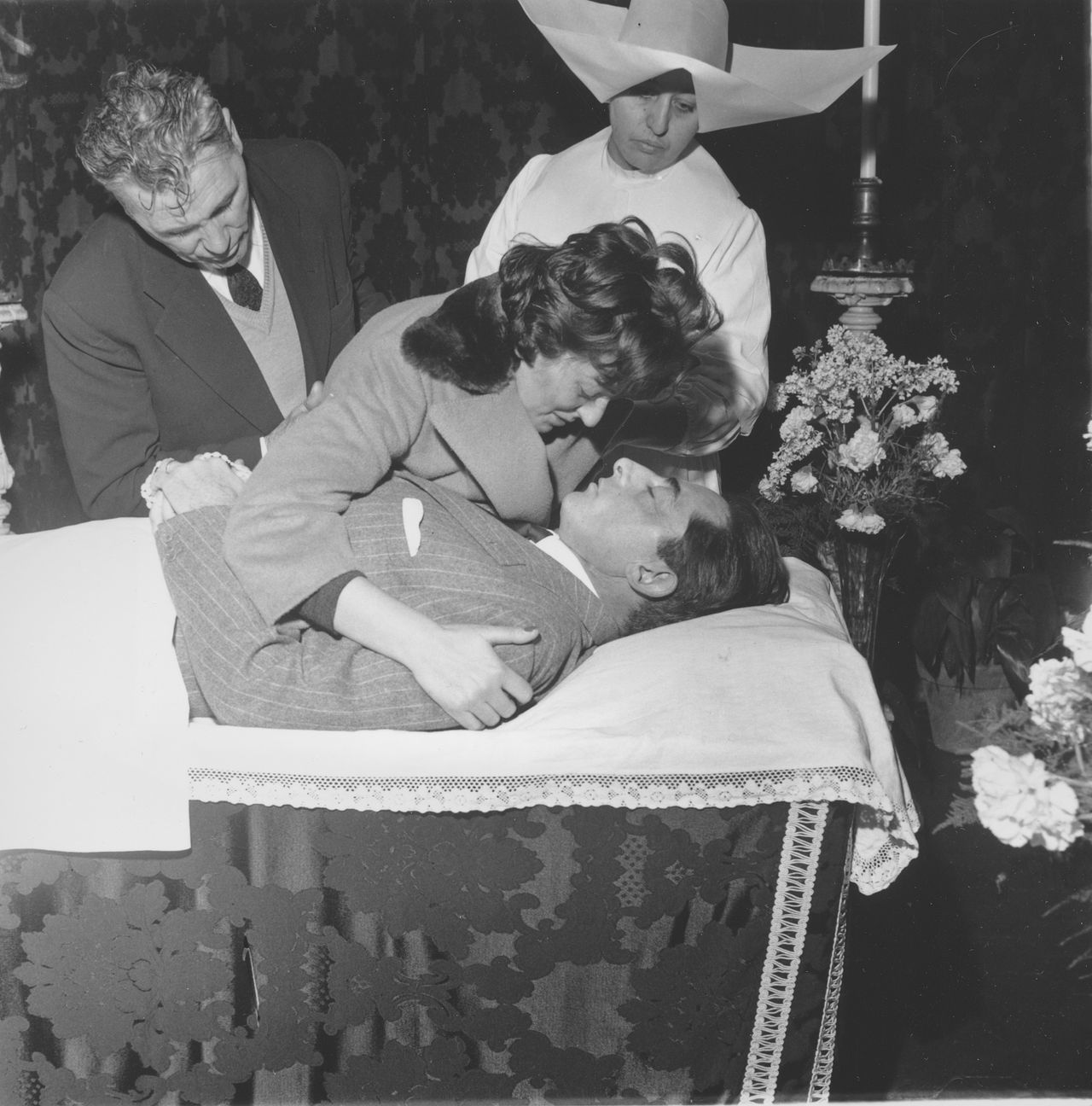 """Giulia Occhini bends to kiss goodbye her companion, Italian cycling champion and two-time Tour de France winner Faust Coppi, who died from a sudden attack of bronchial pneumonia at a hospital in Tortona, Italy, January 2, 1960. Coppi's relationship with Occhini, who was nicknamed """"The Lady in White,"""" caused a national scandal in Italy when in 1953 both left their respective spouses to live together. (AP Photo)"""