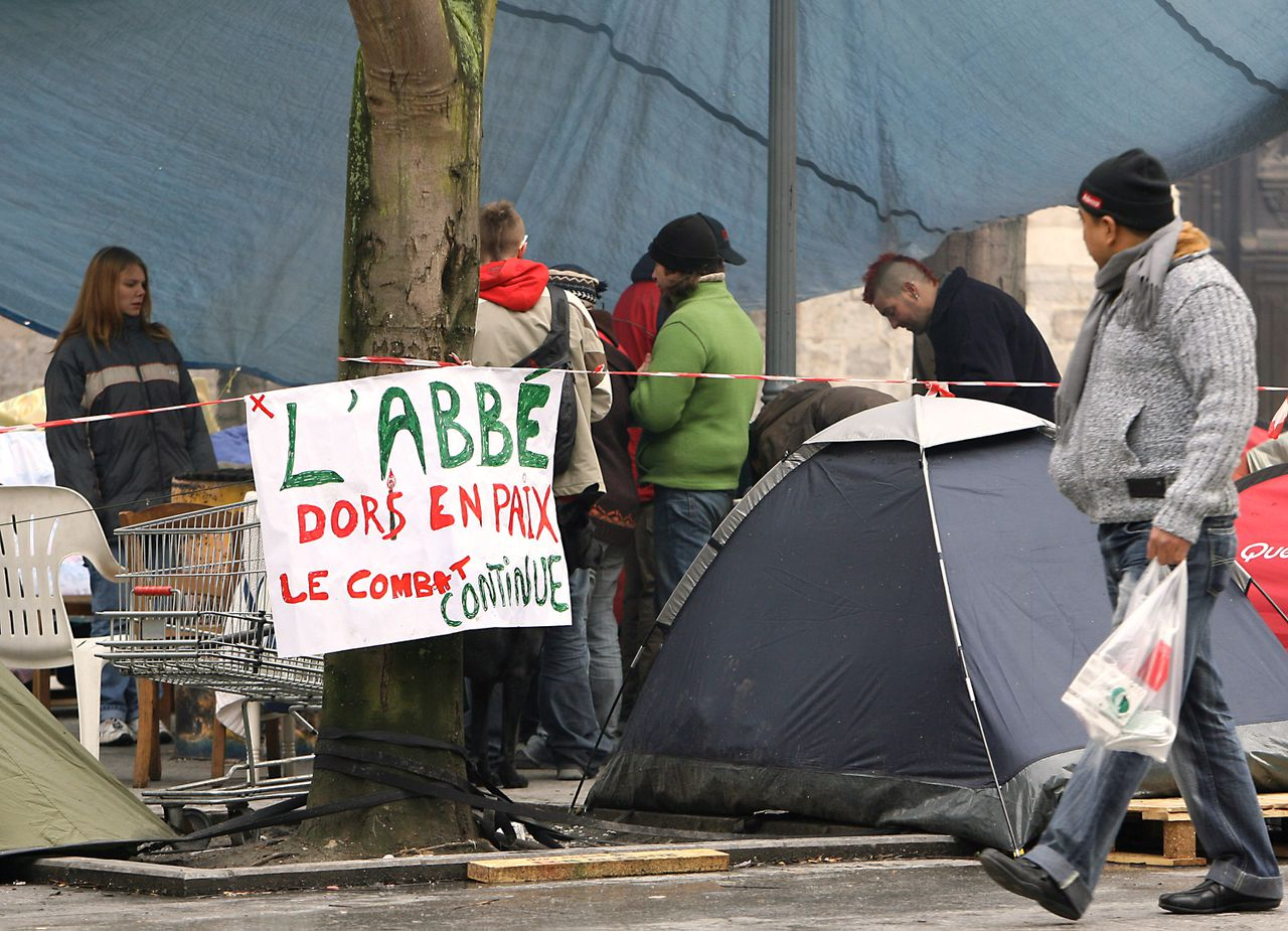 """'Abbé slaapt in vrede, de strijd gaat door'. Opschrift bij een tentenkamp van de actiegroep voor daklozen 'Kinderen van Don Quichotte' in Lille. Foto Reuters A placard reading """" Abbe Pierre sleep in peace"""" is hanged on a tree in an camp set by the Association """"Les Enfants de Don Quichotte"""" (The Children of Don Quixote), 22 January 2007 in Lille, northern France, after the death of Abbe Pierre, a priest who became the conscience of the French nation during more than half a century of campaigns for the homeless, and who died today at the age of 94. AFP PHOTO PHILIPPE HUGUEN"""