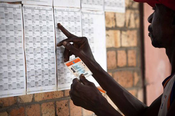 A Congolese voter looks for his name on a list taped on a wall of a polling station in Kinshasa on November 24, 2011. Four days from elections that some analysts doubt can take place on time, Congolese electoral officials were rushing on November 24 to overcome the challenges of crumbling infrastructure and a territory two-thirds the size of Western Europe. The November 28 presidential and parliamentary polls are only the second in the Democratic Republic of Congo since back-to-back wars from 1996 to 2003, and the scars from those conflicts -- together with the country's massive size -- mean officials face a raft of logistical headaches. AFP PHOTO / GWENN DUBOURTHOUMIEU