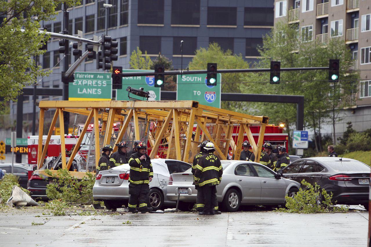 Brandweerlieden aan het werk bij de auto's die zaterdag zijn geraakt door een omgevallen bouwkraan in Seattle