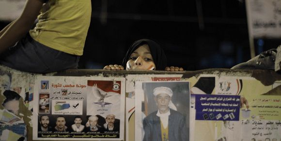 Caption: A Yemeni girl looks from behind a wood fence as the official results of the country's presidential election are being announced at Taghyeer (Change) Square, where protesters have been camping at for around one year to demand the resignation and trial of Yemen's President Ali Abdullah Saleh in Sanaa, Yemen, Friday, Feb. 24, 2012. Yemen's election commission says 65 percent of registered voters in the country cast their ballot for Vice President Abed Rabo Mansour Hadi in the single-candidate election for the nation's new president. (AP Photo/Hani Mohammed)