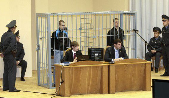 Dmitry Konovalov (L) and Vladislav Kovalyov (R) are seen standing in a guarded cage during a hearing in Minsk, in this September 15, 2011 file photo. Kovalyov and Konovalov were sentenced to death on Wednesday for organising a deadly bomb blast at a metro station in Minsk. REUTERS/Vasily Fedosenko/Files (BELARUS - Tags: CRIME LAW CIVIL UNREST)