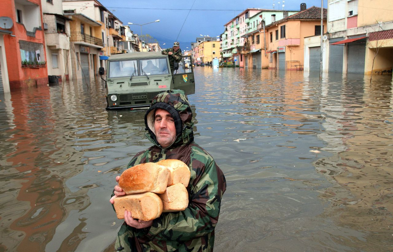 A picture taken on December 4, 2010 shows Albanian soldiers distributing bread in the flooded city of Shkodra. Thousands of people and livestock are being evacuated due to flooding in northwestern Albania. The government declared a state of emergency in the northwestern districts of Albania following days of torrential rain. AFP PHOTO / GENT SHKULLAKU