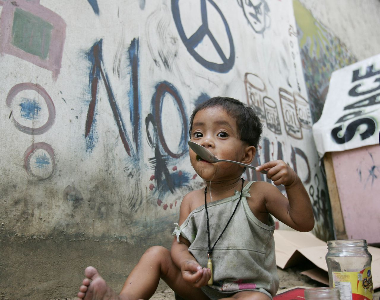 Debat over de voedselcrisis A homeless girl eats her lunch next to a wall covered with a graffiti anti-war message and a peace sign on a street in Manila's Quezon City on Friday April 18, 2008, in the Philippines. The world marks Earth Day on Tuesday April 22, 2008, but this year's theme of water protection is likely to be overshadowed by the looming food and rice crisis. (AP Photo/Bullit Marquez)