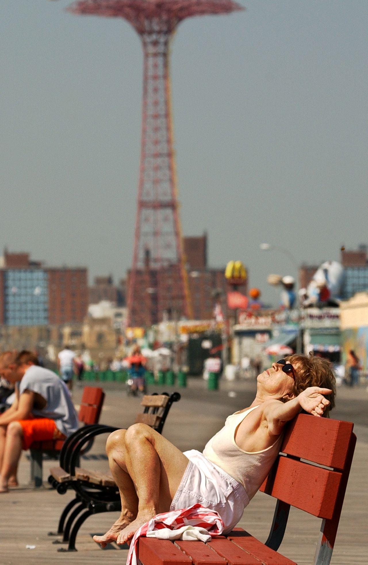A woman basks in the sun on the Coney Island boardwalk Tuesday, April 16, 2002, in New York as record temperatures in the 90's blanketed the metropolitan area on a spring day. It's not even May yet but it feels like July this week as temperatures climb into the 80s and the low 90s from the Plains to the East Coast, drawing people outside in shorts and T-shirts. (AP Photo/Kathy Willens)
