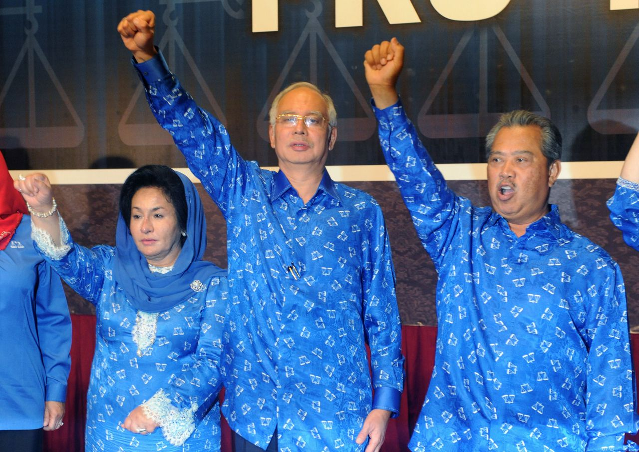 Malaysian Prime Minister Najib Razak (C), his wife Rosmah Mansor (L) and deputy Prime Minister Muhyiddin Yassin celebrate the Barisan Nasional (National Front) coalition electoral victory, on May 6, 2013 in Kuala Lumpur. Country's Election Comission said the ruling Barisan Nasional coalition led by Premier Najib Razak secured 112 parliamentary seats, the threshold required to form a government in the 222-seat chamber. Malaysians voted in record numbers in the general election but the hotly anticipated day was dogged by accusations of electoral irregularities. AFP PHOTO / ROSLAN RAHMAN
