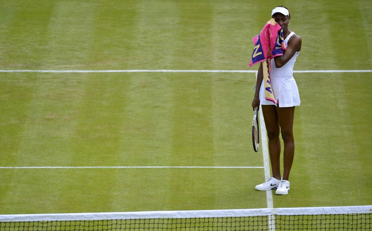 Venus Williams of the U.S. wipes her face during her women's singles tennis match against Elena Vesnina of Russia at the Wimbledon tennis championships in London June 25, 2012. REUTERS/Toby Melville (BRITAIN - Tags: SPORT TENNIS)