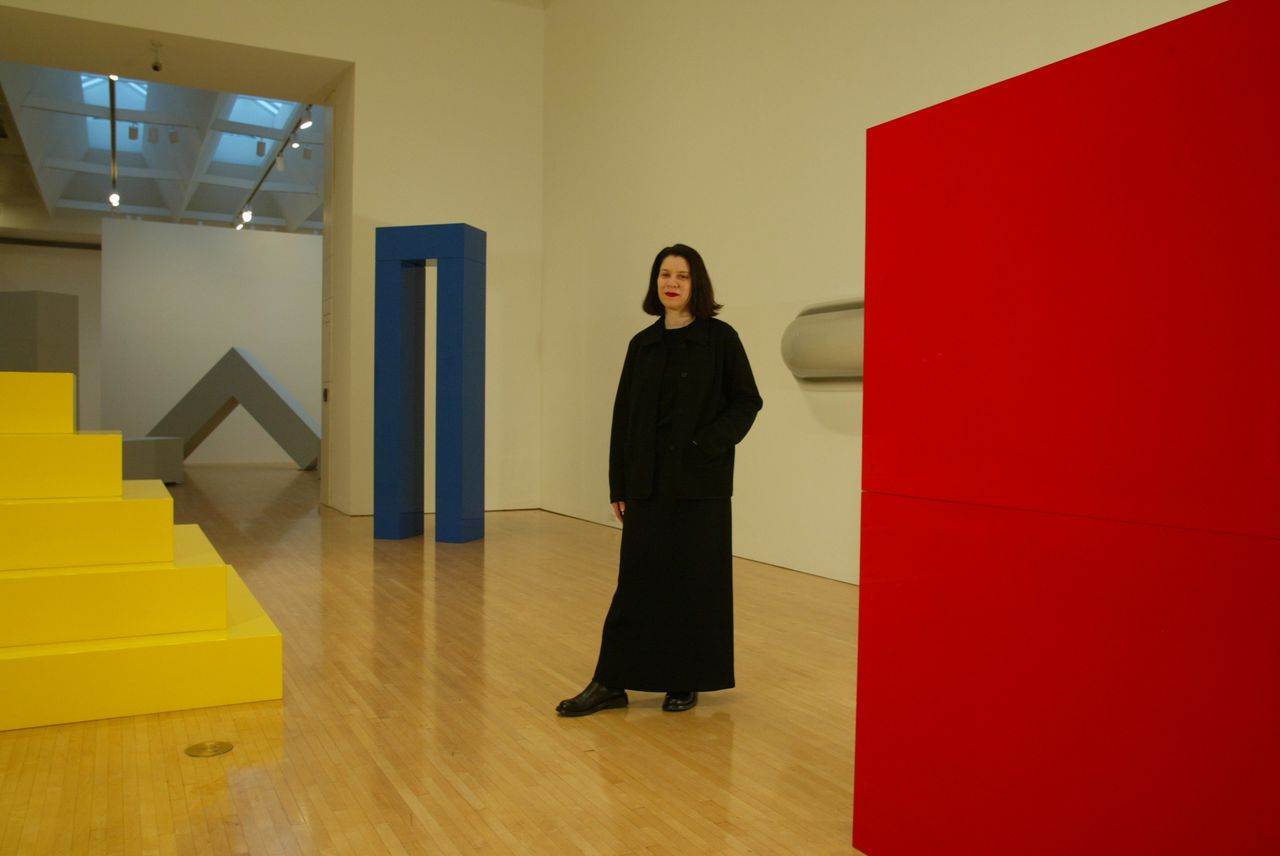 """Ann Goldstein in de door haar samengestelde tentoonstelling A Minimal Future?, over het Amerikaanse minimalisme, die in 2004 plaatsvond in het Museum of Contemporary Art in Los Angeles. (Foto Perry C. Riddle, LAT) """"A Minimal Future? Art as Object 1958-1968"""", is the creation of senior curator Ann Goldstein, pictured, and the most ambitious project of her 20 year tenure at MOCA. The landmark exhibition explores the origins of Minimal art. The yellow, blue and red pieces are by John McCracken. The wall-mounted horizontal piece, at right, vacuum-formed Plexiglass, is by Craig Kauffman. """"L"""" beams in the room at back is by Robert Morris. (Newscom TagID: latphotos014681) [Photo via Newscom]"""