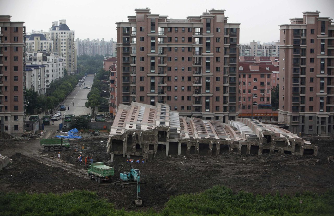 "(Foto Nir Elias/Reuters) A 13-storey apartment building lies on its side after toppling and burying one worker on Saturday, in Shanghai June 29, 2009. Local media reported that 70 people have already paid for apartments in the ""Lotus River Side"" project where one of the buildings toppled during the weekend. REUTERS/Nir Elias (CHINA DISASTER)"