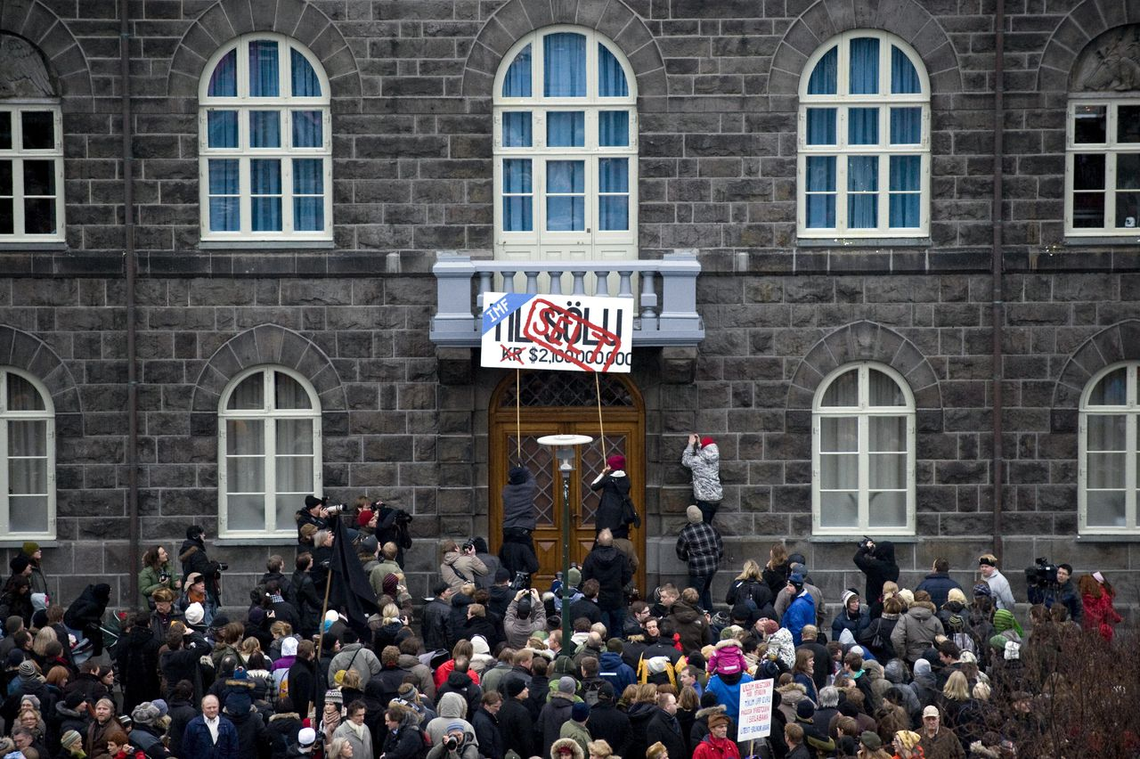 Demonstranten hingen zaterdag aan de gevel van het parlementsgebouw in Reykjavik een bord met: 'Verkocht'. Foto AFP People demonstrate in central Reykjavik during their weekly protest on November 22, 2008. Thousands marched in Reykjavik in what has become a weekly protest over the financial crisis, many charging that an IMF bailout would lay waste to Iceland's generous welfare system. Following the demonstration, a number of protesters also broke into a local police station to demand the release of a demonstrator arrested on November 21, 2008, but no one had so far been arrested, police told AFP. AFP PHOTO / HALLDOR KOLBEINS