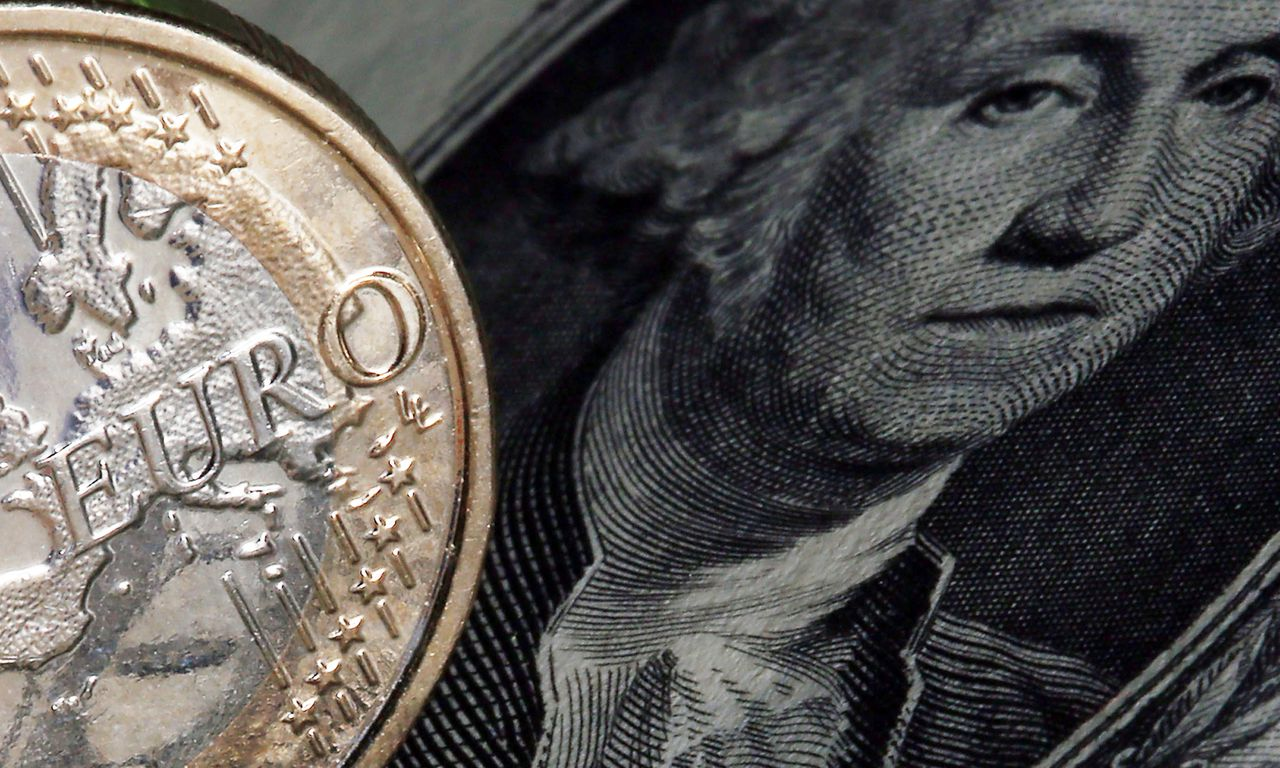 epa04393774 An illustration picture shows a euro coin next to a US dollar bill in Cologne, Germany, 10 September 2014. The euro on 09 September fell to a new 14 month low, costing 1.2860 US dollars. EPA/OLIVER BERG