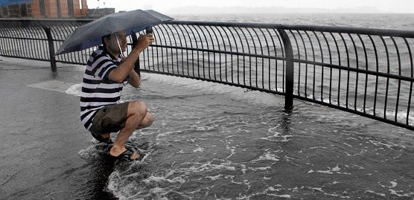 Caption: Water washes over the feet of Battery Park City resident Mickey Alamkhan in Battery Park City's Wagner Park as Hurricane Irene passes through New York, Sunday, August 28, 2011. Seawater surged into the streets of Manhattan on Sunday as Tropical Storm Irene slammed into New York, downgraded from a hurricane but still unleashing furious wind and rain. The flooding threatened Wall Street and the heart of the global financial network. (AP Photo/Jason DeCrow)