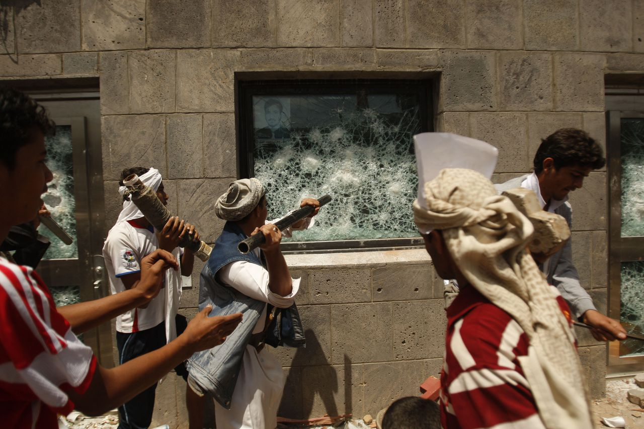 "Yemeni protesters break a window of the U.S. Embassy during a protest about a film ridiculing Islam's Prophet Muhammad, in Sanaa, Yemen, Thursday, Sept. 13, 2012. Dozens of protesters gather in front of the US Embassy in Sanaa to protest against the American film ""The Innocence of Muslims"" deemed blasphemous and Islamophobic. (AP Photo/Hani Mohammed)"