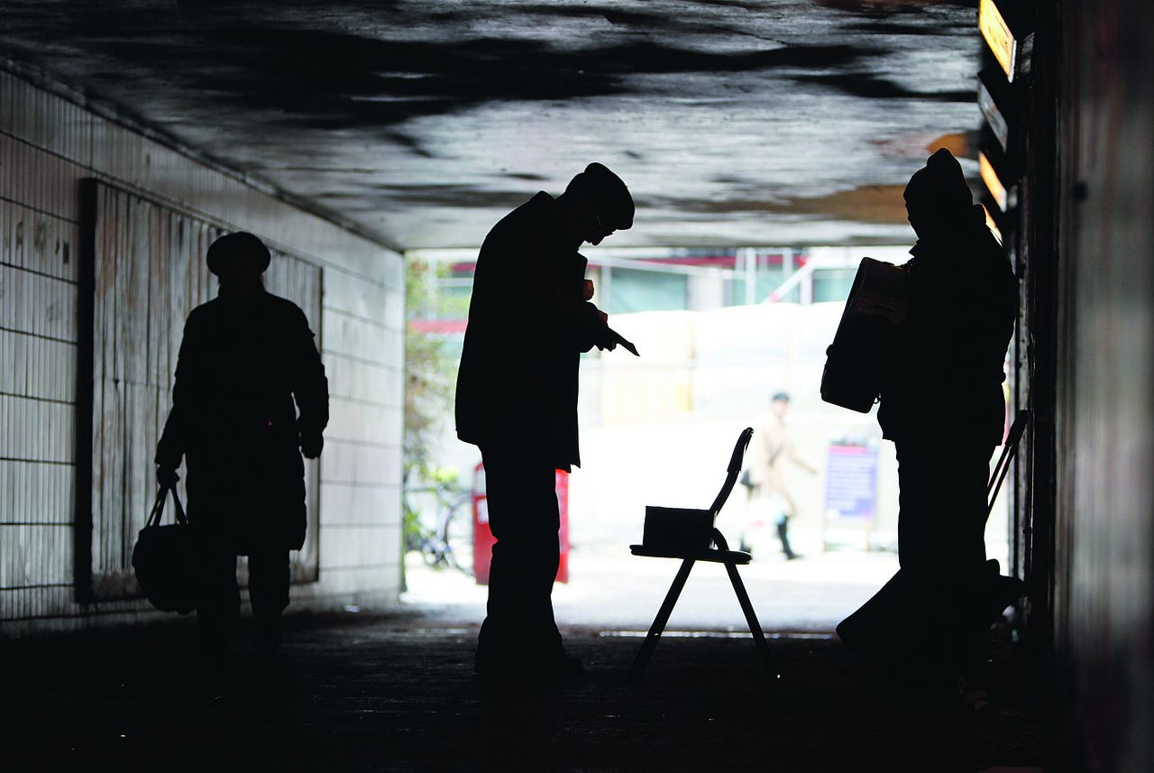 A man gives some money to a busking musician playing in a pedestrian tunnel in Hamburg December 6, 2010. REUTERS/Christian Charisius (GERMANY - Tags: SOCIETY IMAGES OF THE DAY)
