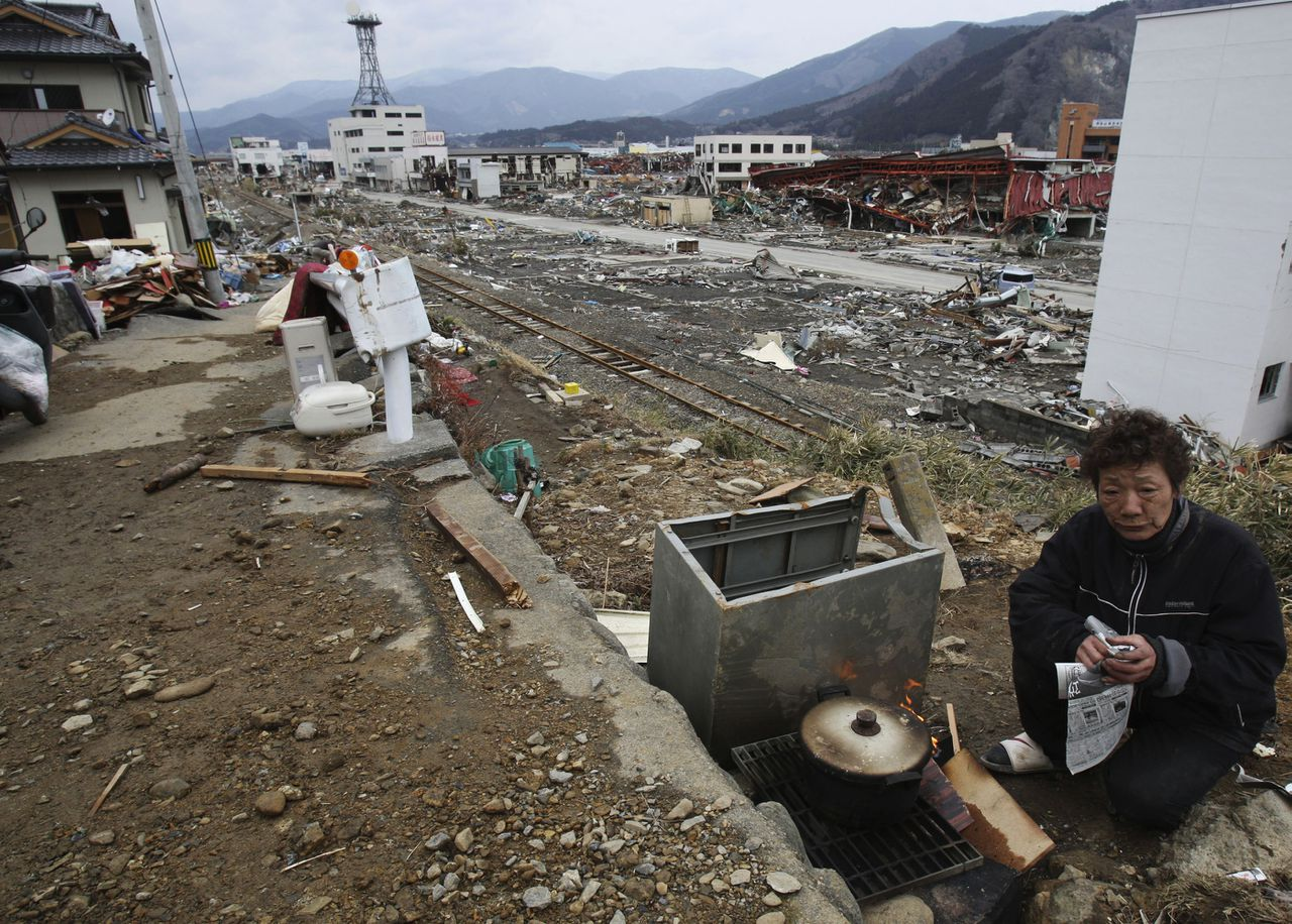 Toshiko Murakami, 62, cooks near her tsunami-hit house in Ofunato, Iwate Prefecture, Japan, Monday, March 21, 2011, after the March 11 earthquake and tsunami. (AP Photo/Koji Sasahara)