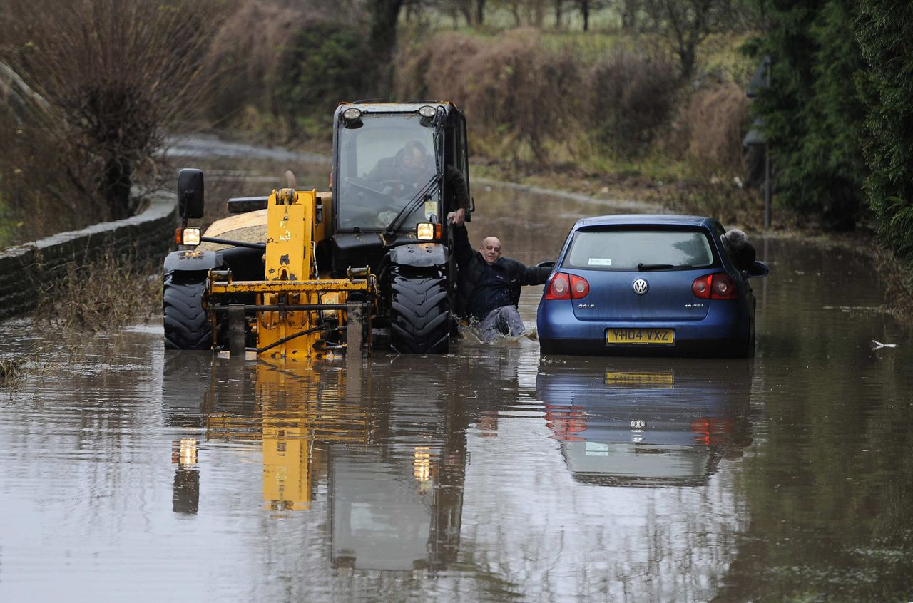 A man climbs from his stranded vehicle in flood water at Milby, northern England December 21, 2012. More rain was forecast overnight on Friday, with more than 260 flood alerts and about 75 flood warnings issued during a period of wet weather, local media reported. REUTERS/Nigel Roddis (BRITAIN - Tags: ENVIRONMENT SOCIETY)