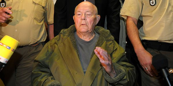 Caption: John Demjanjuk leaves the court after his verdict on May 12, 2011 in Munich, southern Germany. Convicted Nazi guard John Demjanjuk will be freed because of his age, because he cannot travel and pending a possible appeal, a court in Munich said. Earlier, the same court convicted Demjanjuk, 91, of helping to kill almost 30,000 people while a guard at the Sobibor death camp in World War II, sentencing him to five years in prison. AFP PHOTO / CHRISTOF STACHE