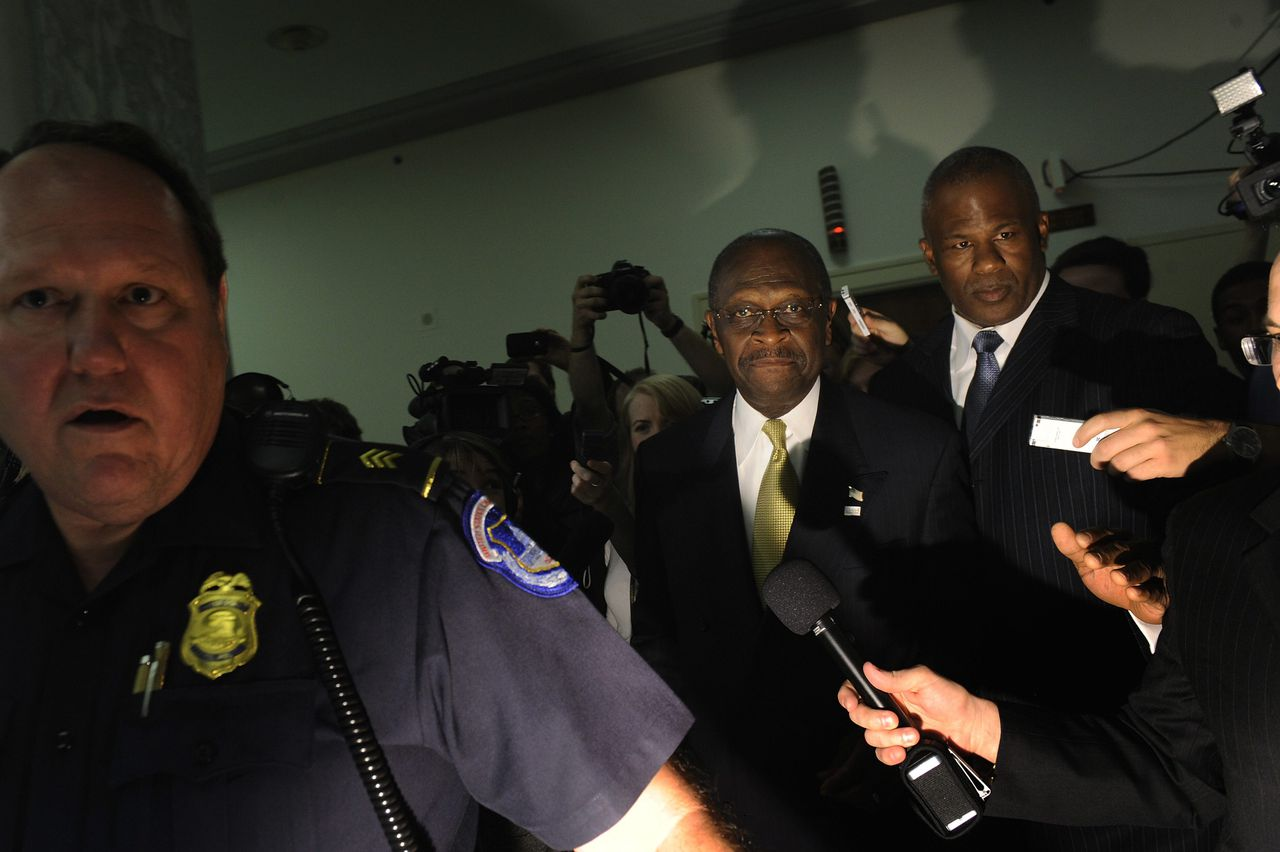 Republican presidential candidate Herman Cain (C) is escorted by U.S. Capitol Police after speaking to legislators in the Congressional Health Care Caucus on Capitol Hill in Washington, November 2, 2011. REUTERS/Jonathan Ernst (UNITED STATES - Tags: POLITICS)