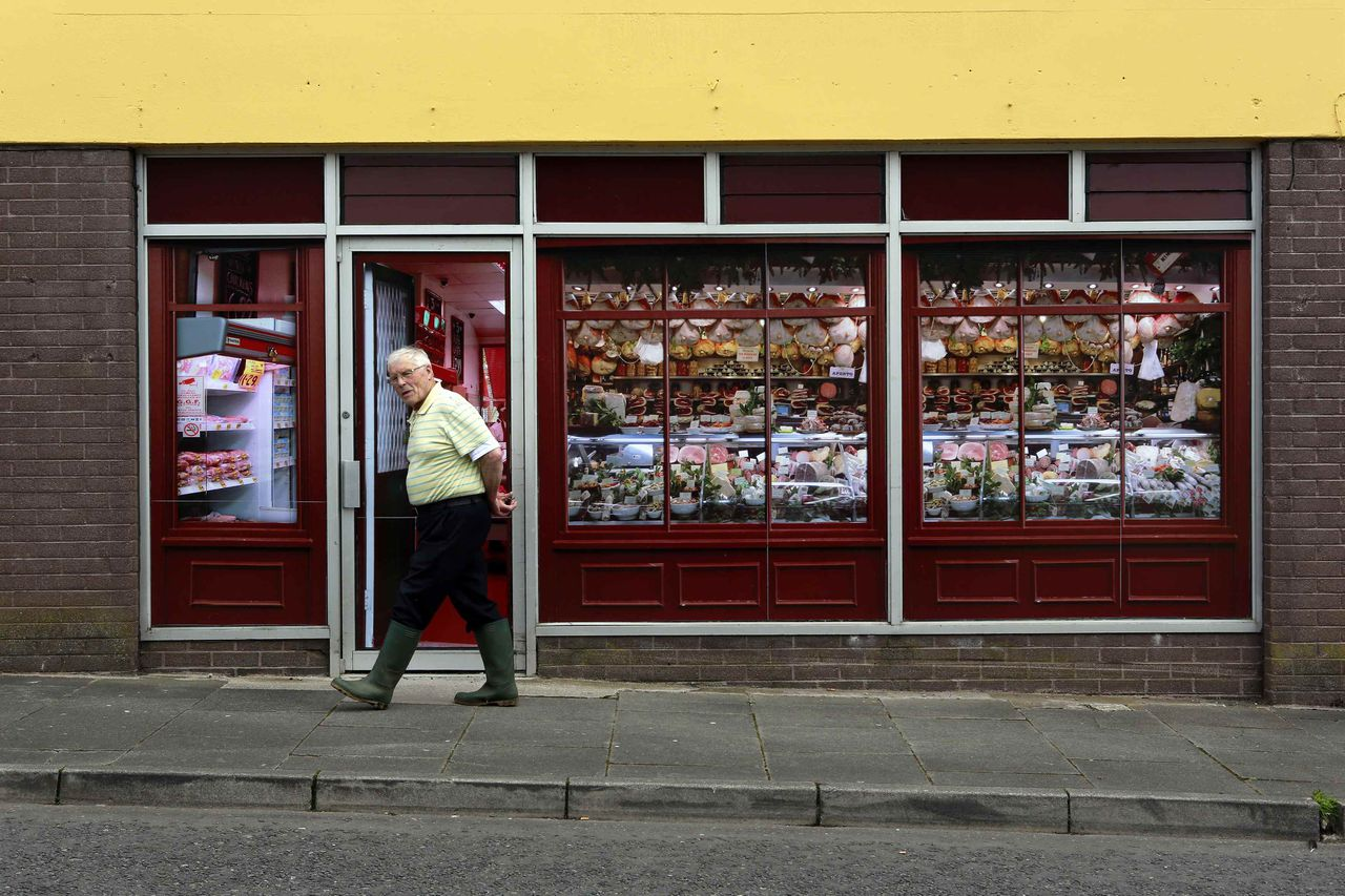 A man walks past a vacant shop, with graphics pasted to the outside to make it look like working butchers shop, in the village of Belcoo, Northern Ireland June 3, 2013. The forthcoming G8 summit will be held at a nearby golf resort. Local councils in Northern Ireland have painted fake shop fronts and covered derelict buildings with huge billboards to hide the economic hardship being felt in towns and villages near the golf resort where G8 leaders will meet this month. REUTERS/Cathal McNaughton (NORTHERN IRELAND - Tags: POLITICS SOCIETY)