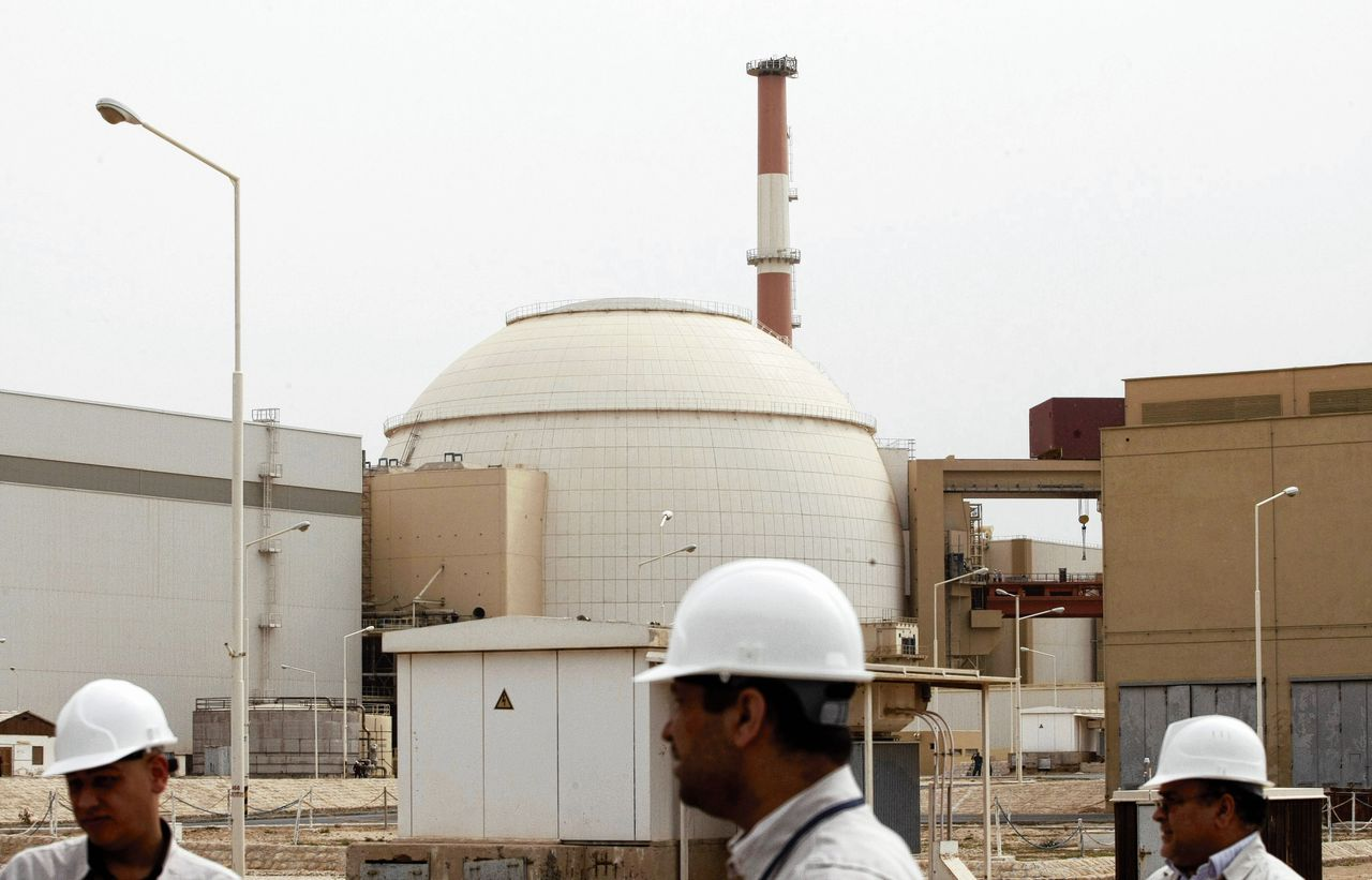 """(FILES) In this file photo taken on February 25, 2009, Iranian technicians walking outside the building housing the reactor of the Bushehr nuclear power plant, in the Iranian port town of Bushehr, 1200 kms south of Tehran. - Iran's foreign minister warned on June 11 of the consequences of waging """"economic war"""" against the Islamic republic through US sanctions, saying those conducting and supporting it could not expect to """"remain safe"""". (Photo by Behrouz MEHRI / AFP)"""