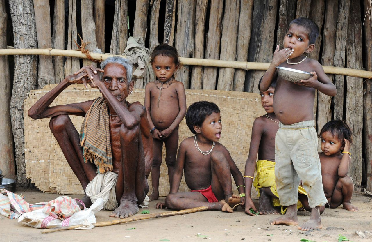 Adivasi's die voor de strijd tussen maoïstische rebellen en veiligheidstroepen uit Chhattisgarh zijn gevlucht, zijn neergestreken in de deelstaat Andhra Pradesh. (Foto AFP) An Indian man and children of the Gothikoya or Muria Gond tribe from Maoist insurgency-hit Chhattisgarh state sit at their temporary abode inside the forest terrain of Khammam district, about 450 km from Hyderabad, on July 2, 2009. Andhra Pradesh state shares 150 km continuous forest border with Chaattisgarh, origin of a 30,000 exodus of Gothikoya tribals fleeing clashes, which began in late 2005, between Maoist Naxalites and the Chhattisgarh government. The authorities says these settlements are illegal and have forcibly evicted hundreds of displaced persons by repeatedly burning down their hamlets. TOPSHOTS AFP PHOTO/Noah SEELAM