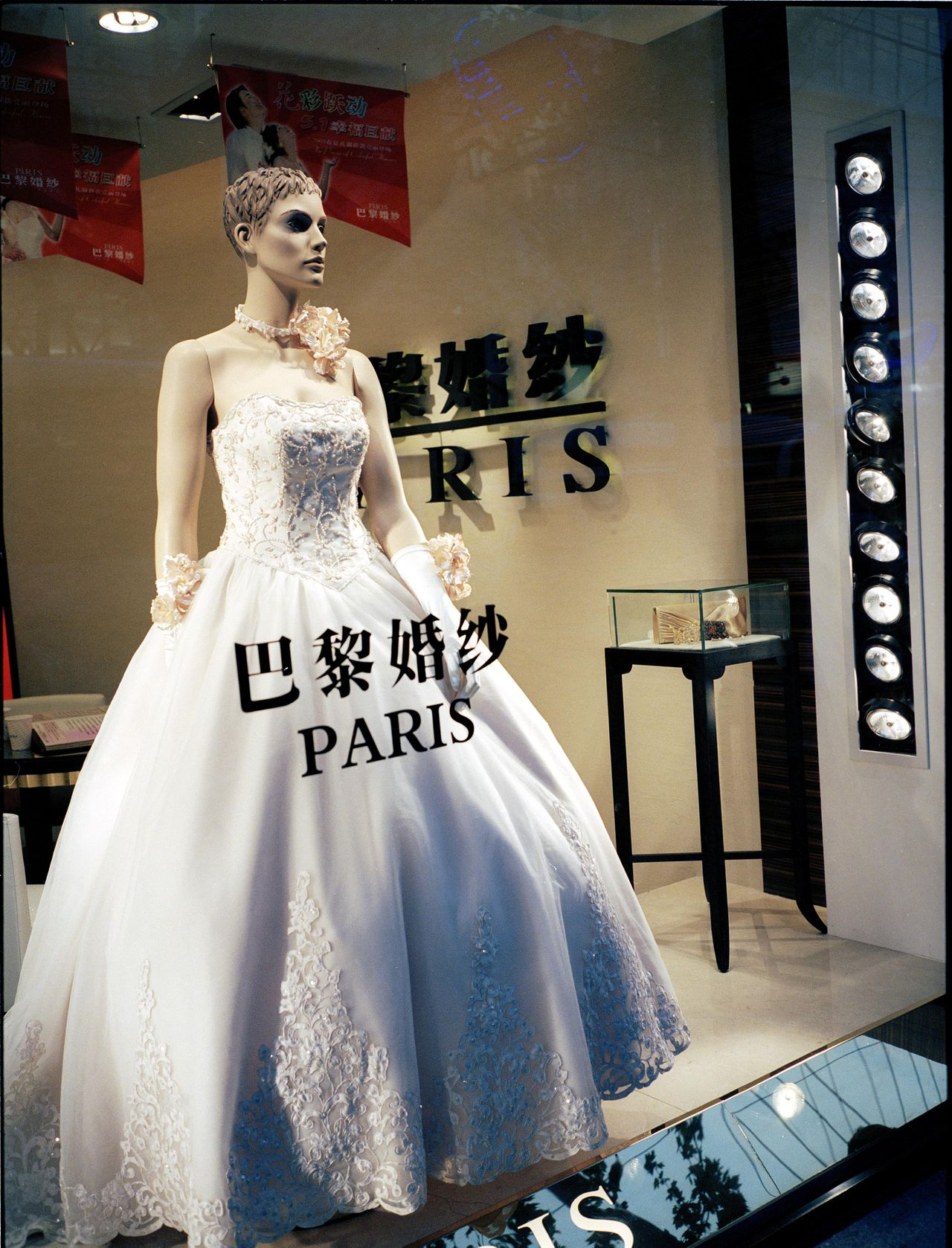 De Chinese trouwindustrie is goed voor een omzet van 210 miljard euro. Een winkel met trouwjurken in Wuhan. (Foto AFP) Shanghai, China Mei 2005 Wedding is big Bussines Foto : Marleen Daniels/HH