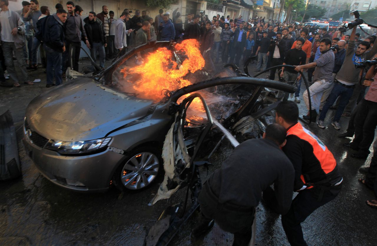 Palestinians extinguish fire from the car of Ahmaed Jaabari, head of the military wing of the Hamas movement, the Ezzedin Qassam Brigades, after it was hit by an Israeli air strike in Gaza City on November 14, 2012. The top Hamas commander Ahmed al-Jaabari was killed in an Israeli air strike , medics and a Hamas source told . AFP PHOTO/MAHMUD HAMS
