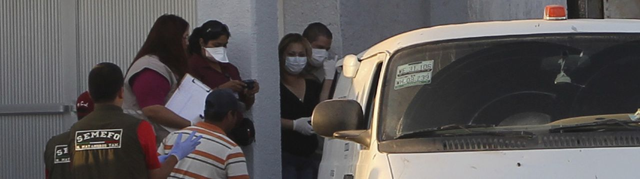 Forensic workers prepare to transfer bodies from a van into a large truck, not seen, in the northern border city of Matamoros, Mexico Wednesday April, 6, 2011. At least fifty-nine bodies were found buried in a series of pits in the northern Mexico state of Tamaulipas, near the site where suspected drug gang members massacred 72 migrants last summer, officials said.(AP Photo/Rubios News)