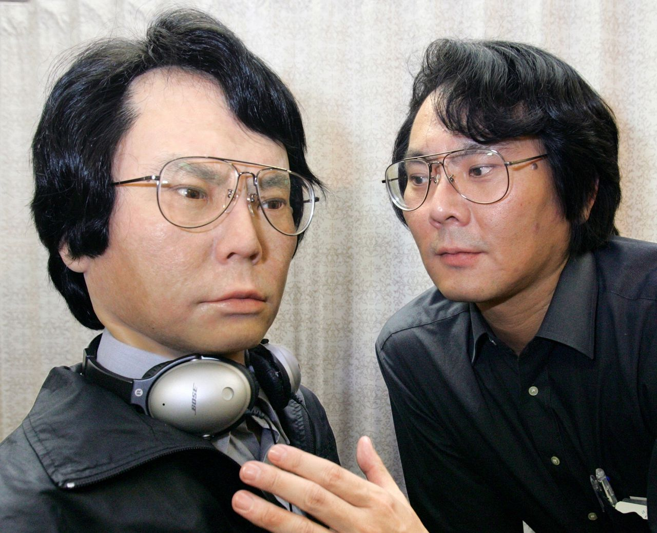 De Japanse robotwetenschapper Hiroshi Ishiguro ontwierp een kopie van zichzelf, juli 2006 (kosten: 258.000 dollar). Foto AP Prof. Hiroshi Ishiguro, right, of Osaka University looks at an android robot that looks exactly like him in Kyoto, western Japan, on Thursday July 20, 2006. The robot, which cost about 30 million yen (US$258,000) to develop, is remote-controlled to speak and can wear carbon copy expressions of Ishiguro. The robot Ishiguro, its face covered with silicone rubber, stands at 175 centimeters, the height of the professor, who completed the robot based on a real person to collect basic data for a future robot which can communicate with the human beings. (AP Photo/Asahi Shimbun, Hiroyuki Yamamoto) ** JAPAN OUT NO SALES ONLINE OUT MANDATORY CREDIT **