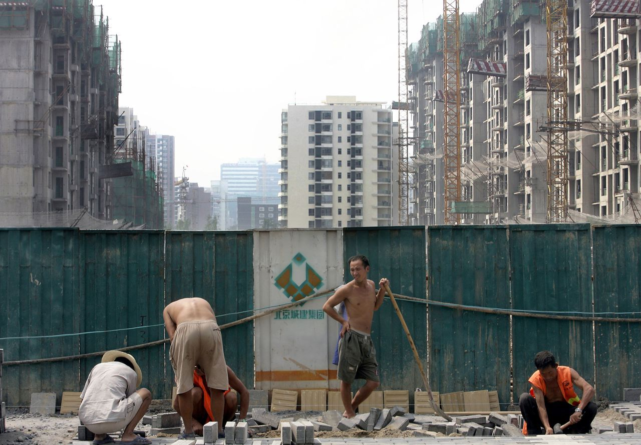 Nieuwbouw in Peking. De bouwvakkers zijn veelal plattelanders. De bewoners behoren tot China's nieuwe stedelijke middenklasse. Foto AFP Chinese labourers pave a street outside a new luxury condominium project in Beijing 06 August 2006. Foreign investors are seen as playing a key role in the China's housing boom, investing in some 3.4 billion USD worth of property in 2005, accounting for 15 percent of total property purchases, and building luxury housing to attract rich overseas buyers and wealthy Chinese, even as cities run short of low-cost housing for ordinary Chinese, causing prices to rise at the same time that the unsold property stock grew 23.8 percent in the first quarter of 2006. AFP PHOTO/GOH CHAI HIN