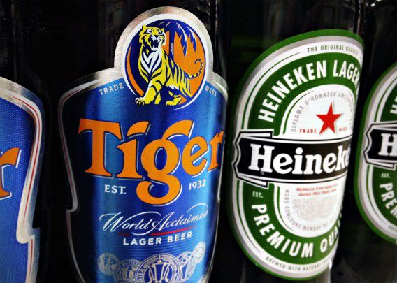 Bottles of Tiger and Heineken beers are pictured on the shelf of a grocery store in Singapore in this July 20, 2012 file photograph. Heineken is expected to sweeten its $4.1 billion offer to Fraser and Neave (F&N) to win control of Tiger